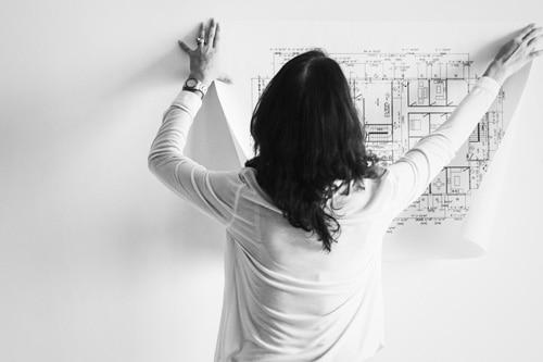 Frau im Büro hängt einen Plan an die Wand
